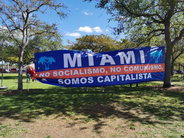 """A banner at the FRWND Republican Unity Picnic states, """"Miami. No socialism. No communism. We are Capitalists."""" (Zoe Chin/SFMN)"""